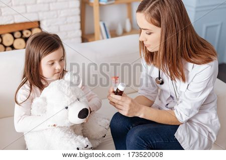 Your every day norm. Professional pleasant doctor holding pills while giving tipps to little girl who is sitting with her fluffy toy