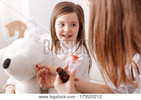 I want him to recover. Cheerful little girl holding her fluffy toy while her mother pretending to be a doctor and giving pills