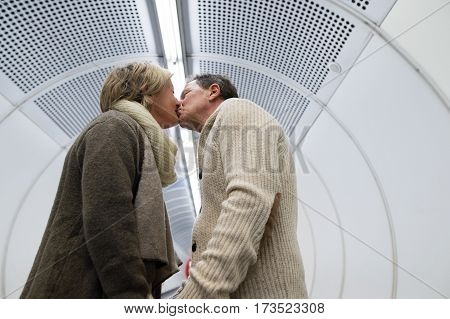 Beautiful senior couple walking in the hallway of subway in Vienna pulling a trolley luggage, kissing.