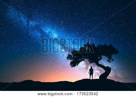 Night landscape with Milky Way and silhouette of man under the tree growing from the rock on the mountain. Nature background with starry sky and beautiful galaxy. Blue Milky Way and man. Universe