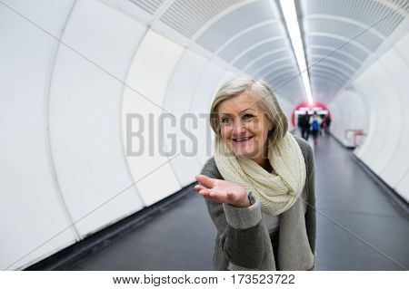 Beautiful senior woman in hallway of subway in Vienna saying goodbye, sending someone a kiss.