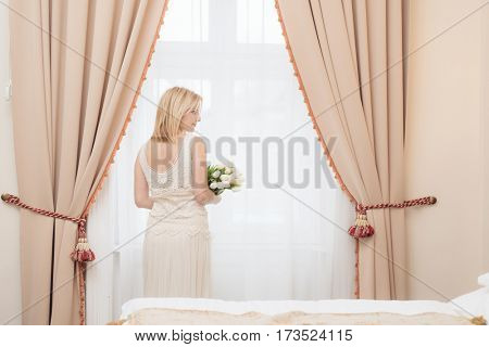Back view of young bride looking out of window in elegant hotel room
