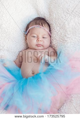 Portrait Of A Newborn Girl With A Pink-and-blue Skirt And Hair Decoration Rim On The Head. Gentle Ph