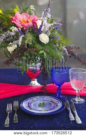Table setting in vintage style is decorated with flowers in pink and blue colors