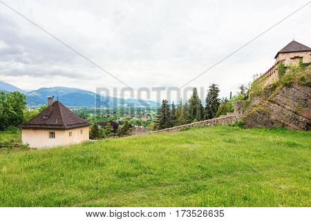 Panoramic view over stadt salzburg with ancient castle and small house, green grass, rainy day and mountains, austria