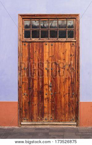 Outdoor wooden varnished orange door vertical view