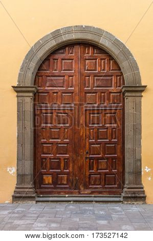 Outdoor wooden varnished brown door with concrete arch vertical view