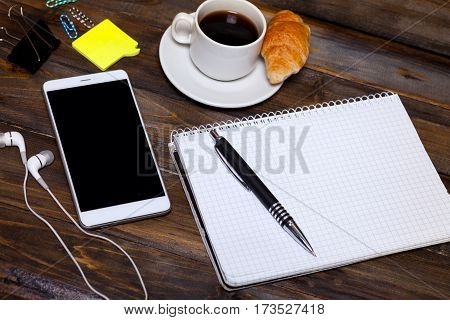 White Mobile Phone On Wooden Wooden Background With Headphones, Cup Of Coffee, Croissant And Station