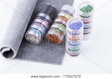 Seed beads in glass tubes and grey beading mat for beading on white background. Selective focus.
