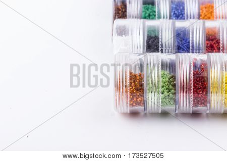 Glass seed beads storage system on white background. Hobby handmade fine arts. Selective focus.