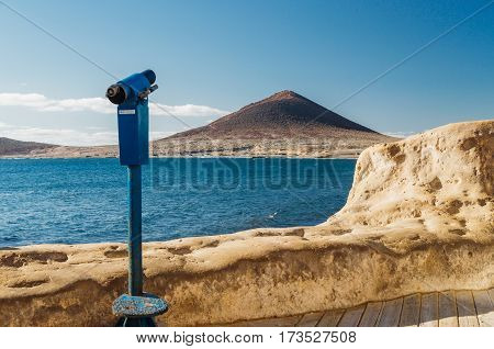 Touristic sightseeing telescope. Atlantic ocean and Montana Roja on background. Tenerife island Spain