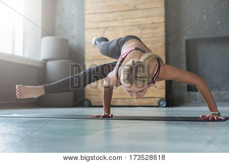 Handstand balance. Young slim blond woman in yoga class making asana exercises. Healthy lifestyle in fitness club.