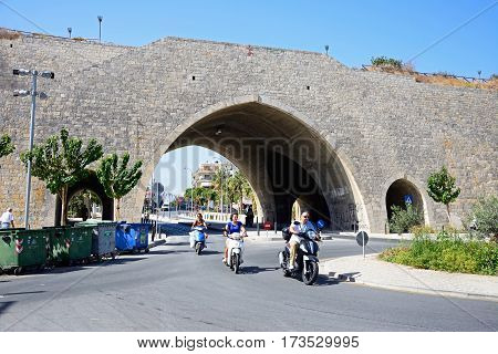 HERAKLION, CRETE - SEPTEMBER 19, 2016 - Arch in the city defence wall with people riding mopeds in the foreground Heraklion Crete Greece Europe, September 19, 2016.
