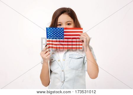 Representing my native country. Shy little charming child demonstrating the American flag while expressing positive emotions and standing against white background