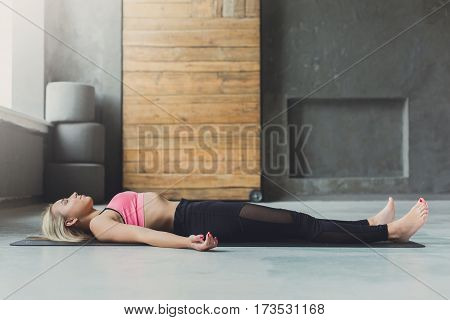 Young slim blond woman in yoga class lay on floor. Girl do meditation corpse pose, savasana for relaxation. Healthy lifestyle in fitness center