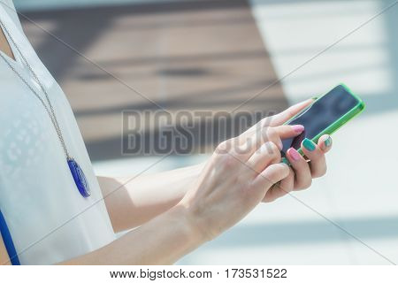Detail of a girl using cellphone outdoors.