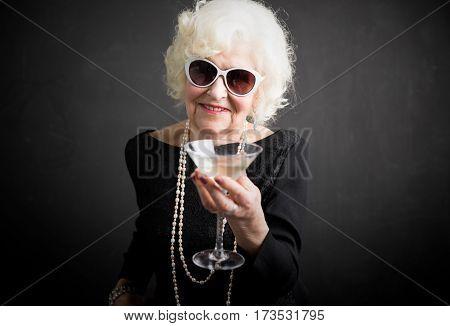 Cool grandma having a drink in glass