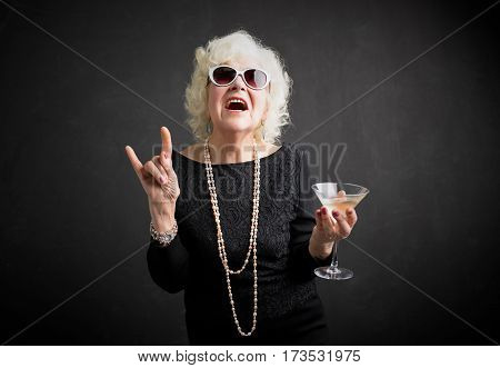 Cool grandmother with sun glasses and drink in hand