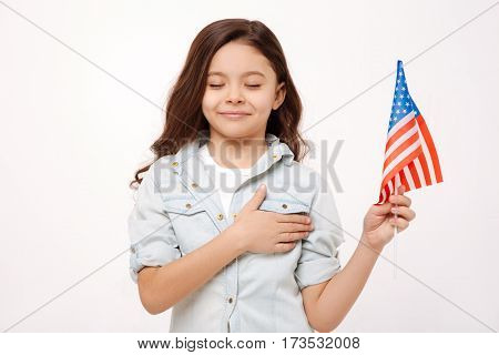 Loving my native country. Cute little happy girl holding the American flag and touching her chest while expressing happiness and standing with closed eyes isolated in white background