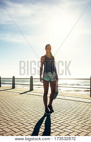 Full length shot of young woman walking on the sea side promenade. Female runner out in the morning.