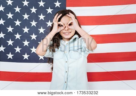 Having fun. Amused cheerful delighted girl having fun and expressing joy while standing against American flag