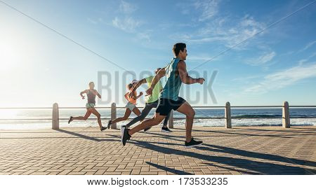 Young Runners Sprinting On The Ocean Front Path