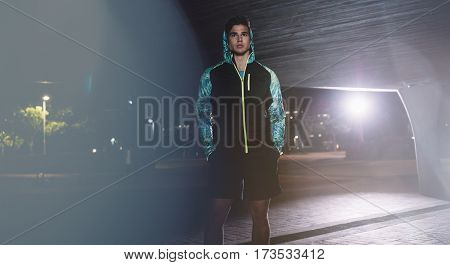 Portrait of urban male runner standing under bridge at night. Handsome young sportsman standing on the street.