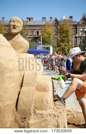Khabarovsk Russia - August 30 2014: Sand sculpture festival - an artist working on a man figure. Outdoor creative art competition