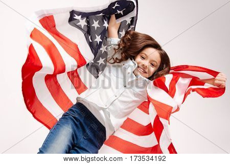 Sharing sunny mood. Joyful flexible happy girl having fun and expressing positivity while jumping against white background and holding the American flag