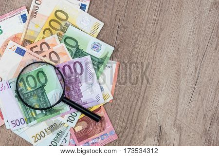 Different Euros Banknotes Under Magnifying Glass On Desk.