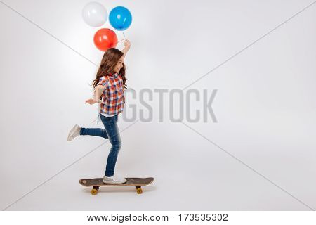 Practicing new skills. Skillful gifted artistic child expressing joy and holding colorful balloons while standing against white background and using skateboard