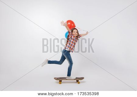 Demonstrating new skills. Skilled gifted happy child expressing joy and holding colorful balloons while standing against white background and u skateboarding