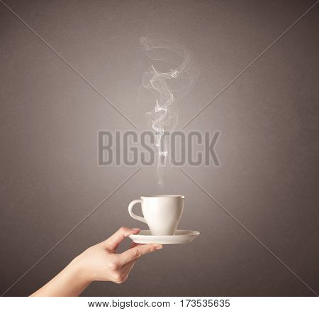 Young female hand holding steaming coffee cup