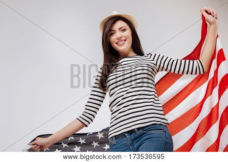 Representing beauty of our country . Optimistic charismatic positive woman smiling and celebrating national holiday while standing against white background and holding American flag