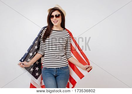 Representing citizens of our country . Charismatic slim positive woman smiling and celebrating national holiday while standing against white background and holding American flag