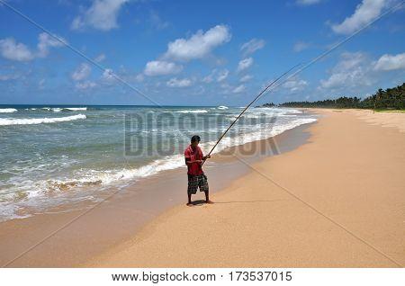 MORATUVA/ SRI LANKA - OCTOBER 3, 2012. A lone fisherman with a fishing rod on the beach. Sri Lanka.