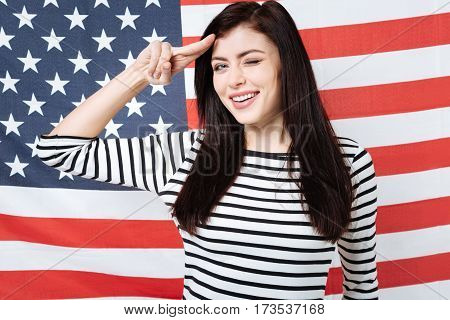 Lets having fun together. Happy amused cheerful woman smiling and celebrating American national holiday while standing against American flag and putting fingers to her temple