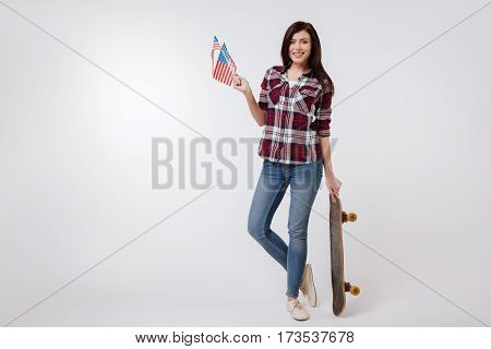 Enjoying this life. Slim beautiful cheerful woman smiling and celebrating American national holiday while standing against white background and holding American flag and skateboard