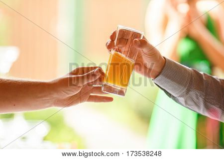 Man's Hand Reach Out A Glass With Fresh Juice To Another Man