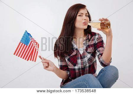 Celebrating holiday. Charismatic positive overjoyed woman smiling and celebrating American Independence day while sitting against white background and holding American flag and drinking beverage
