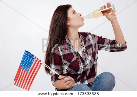 My celebration of the national holiday . Funny positive overjoyed woman smiling and celebrating national holiday while sitting against white background and holding American flag and drinking beverage