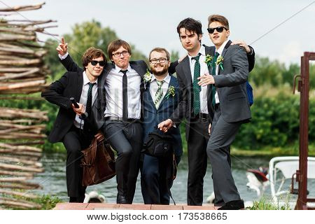 Stylish guys and groom in black suit look ready for a party