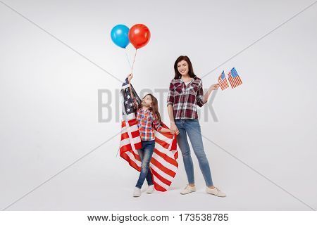 Enjoying family weekend. Positive optimistic delighted mother smiling and celebrating national holiday while standing with her daughter against white background and holding American flag and balloons