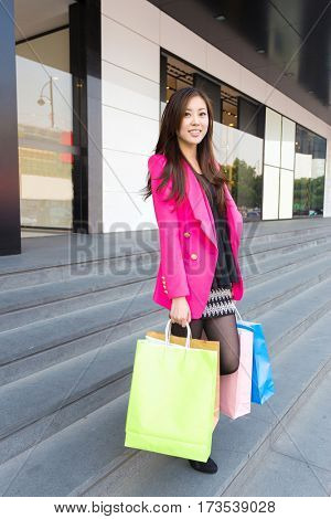 beautiful chinese girl with colorful shopping bags front of entrance of shopping mall