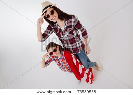 Joyful family celebration. Lively stylish merry mother celebrating American holiday with her daughter while standing isolated in white background and holding American flag