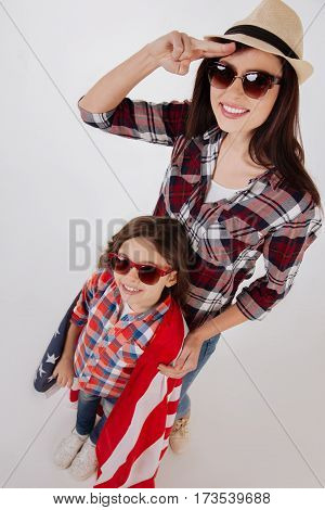 Amazing family weekend . Funny stylish happy sisters celebrating American national holiday while standing isolated in white background and holding American flag