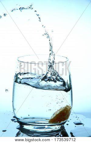 water splash in glass from falling slices of mandarin