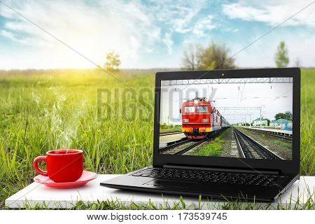 Laptop and cup of hot coffee on the background picturesque nature, outdoor office. Traveling by train. Travel concept. Business ideas. Choice of travel. Landscape at sunset