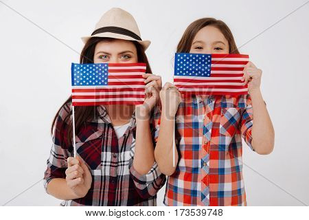 Happy family weekend . Playful stylish happy sisters celebrating American national holiday while standing against white background and holding American flag