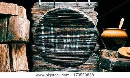 Honey in clay pot with lid and spoon on wood stump. Other stumps in stack. Round wood sign with text 'Honey'. Isolated over black